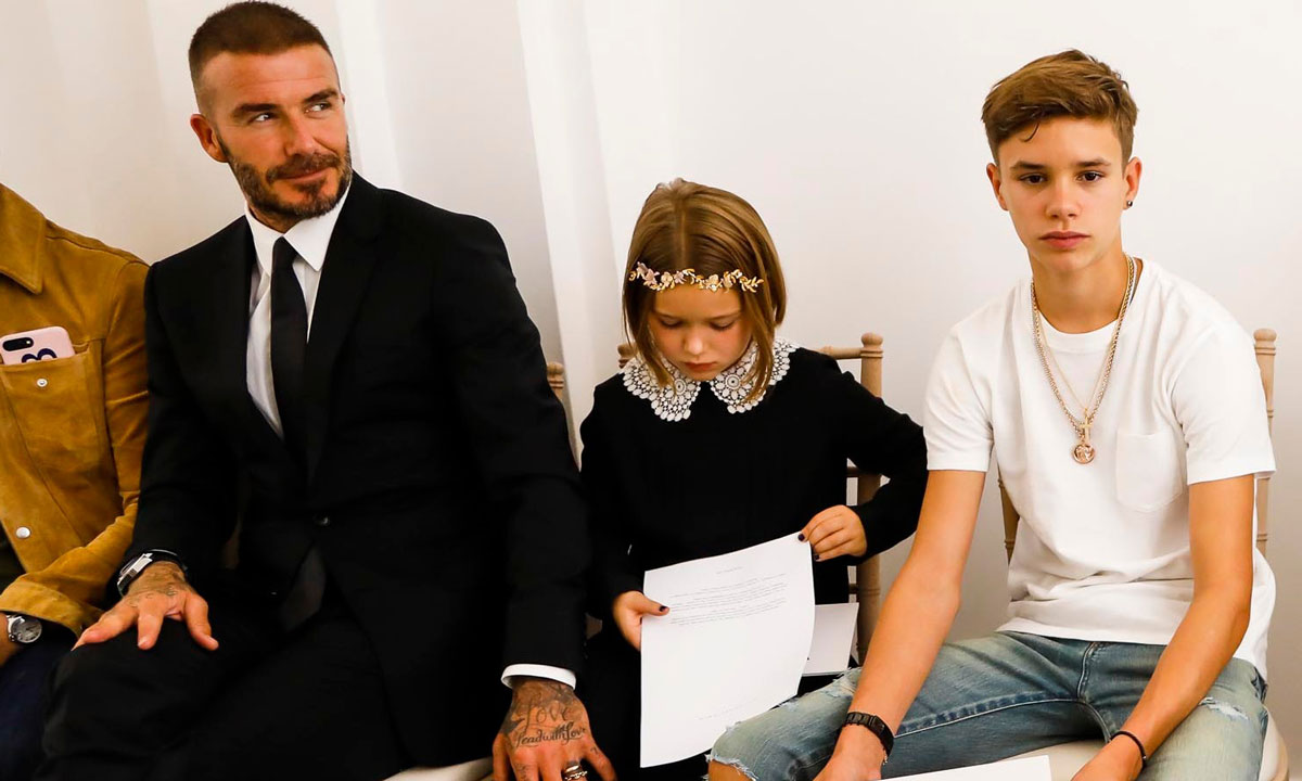 David Beckham sits with Harper at fashion show