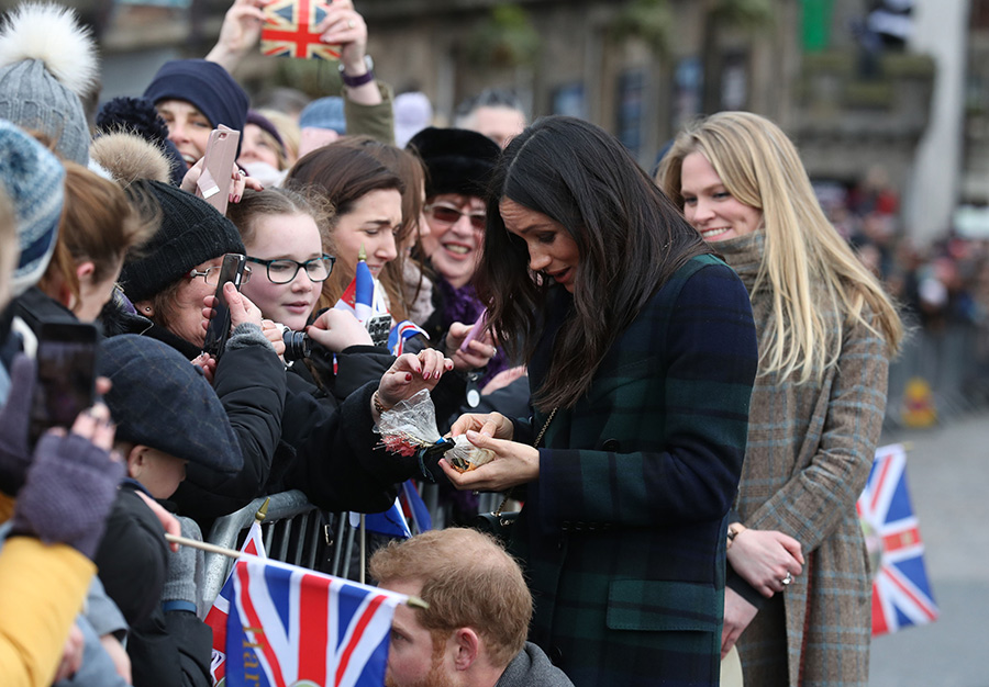 Meghan Markle admires a tidbit from the crowd