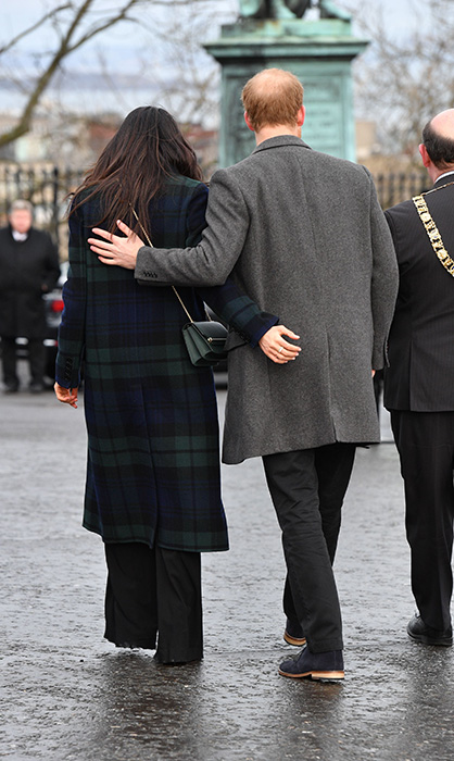 Meghan Markle and Prince Harry with their arms around each other